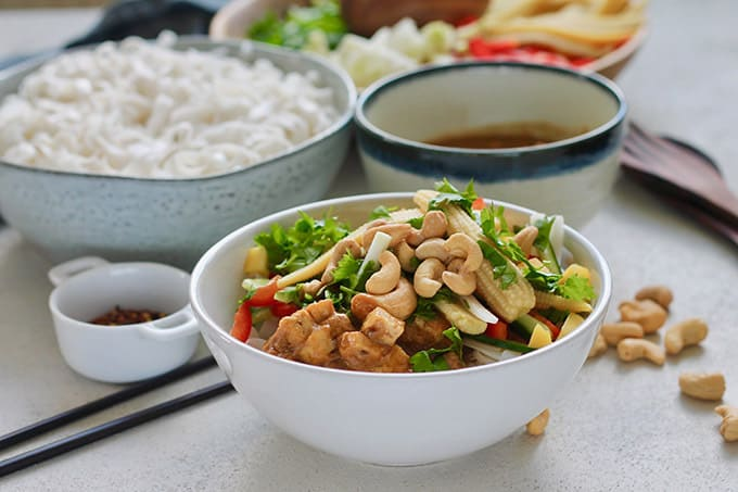 A white bowl with cold rice noodle salad topped with peanut sauce and cashews, with scattered cashews and chopsticks in the background