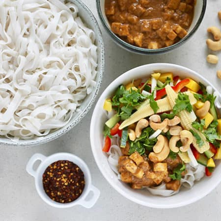 An overhead shot of cold rice noodle salad in a white bowl with chopsticks, cashews, and chili flakes to the side