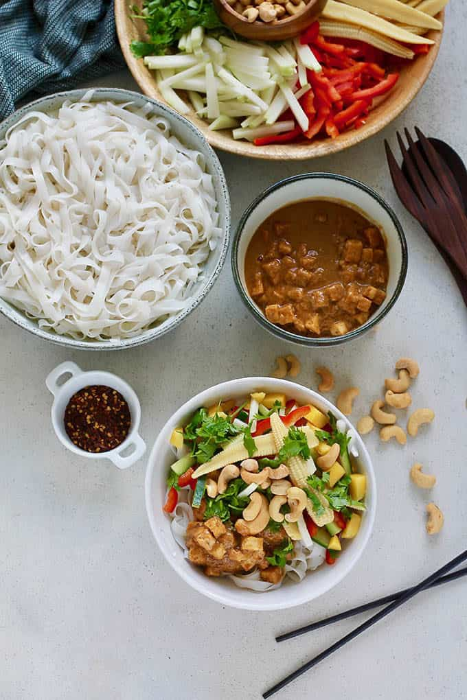 A white bowl with cold rice noodle salad on a grey background, with a bowl of rice noodles, peanut sauce and tofu, and a platter of vegetables in the background
