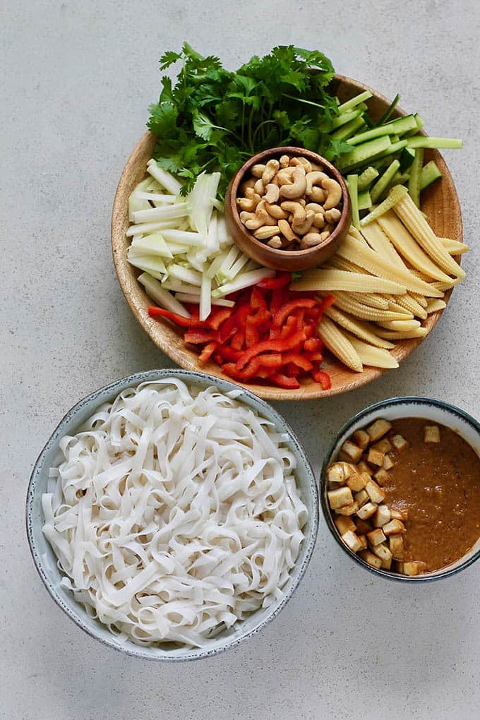 A large bowl of rice noodles, a smaller bowl with peanut sauce and tofu, and a wooden platter with vegetables and cashews on a grey background