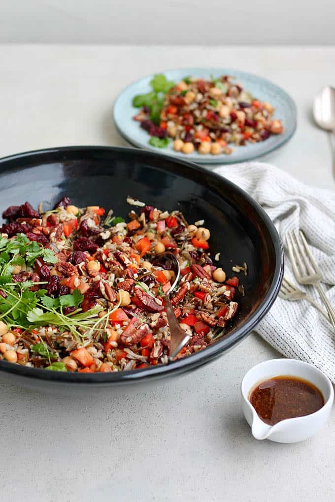 A black bowl of wild rice salad with a pot of dressing and a white tea towel to the side