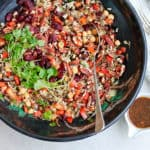 overhead photo of wild rice salad with chickpeas and cranberries in a black bowl
