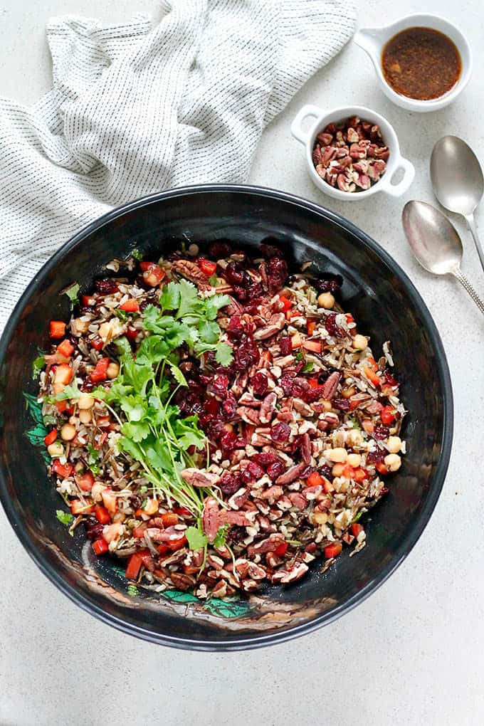 overhead photo of wild rice salad in a black bowl