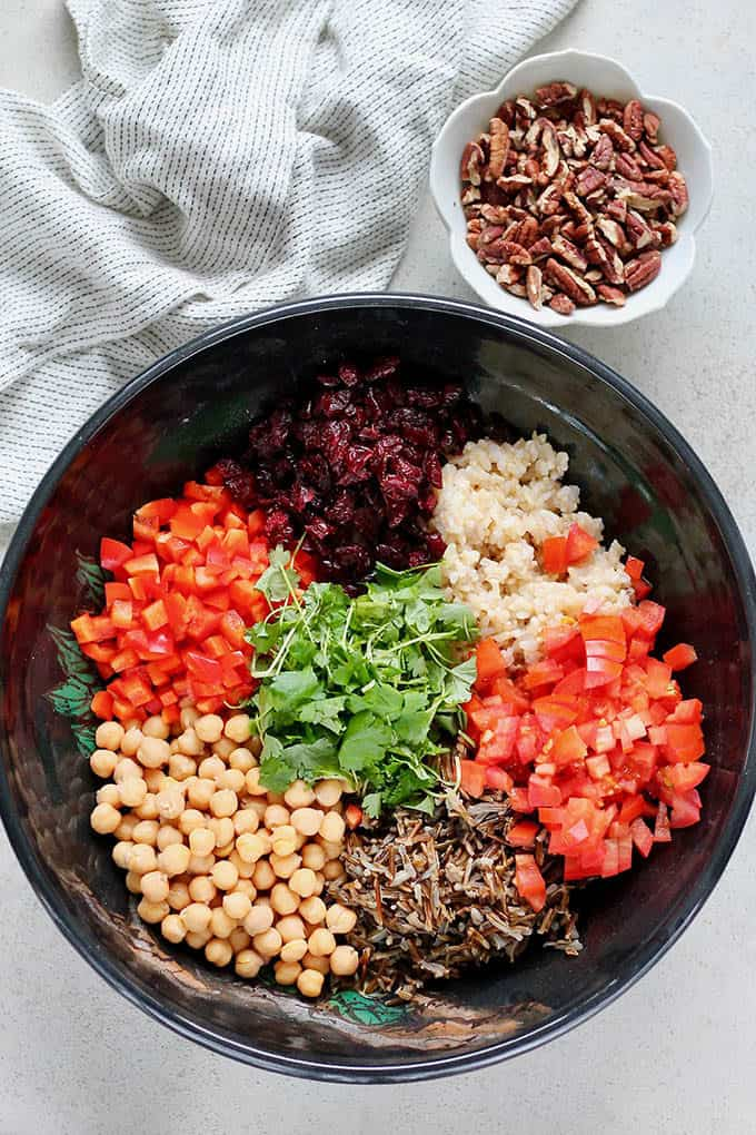 overhead photo with all of the ingredients for a wild rice salad divided into a black bowl