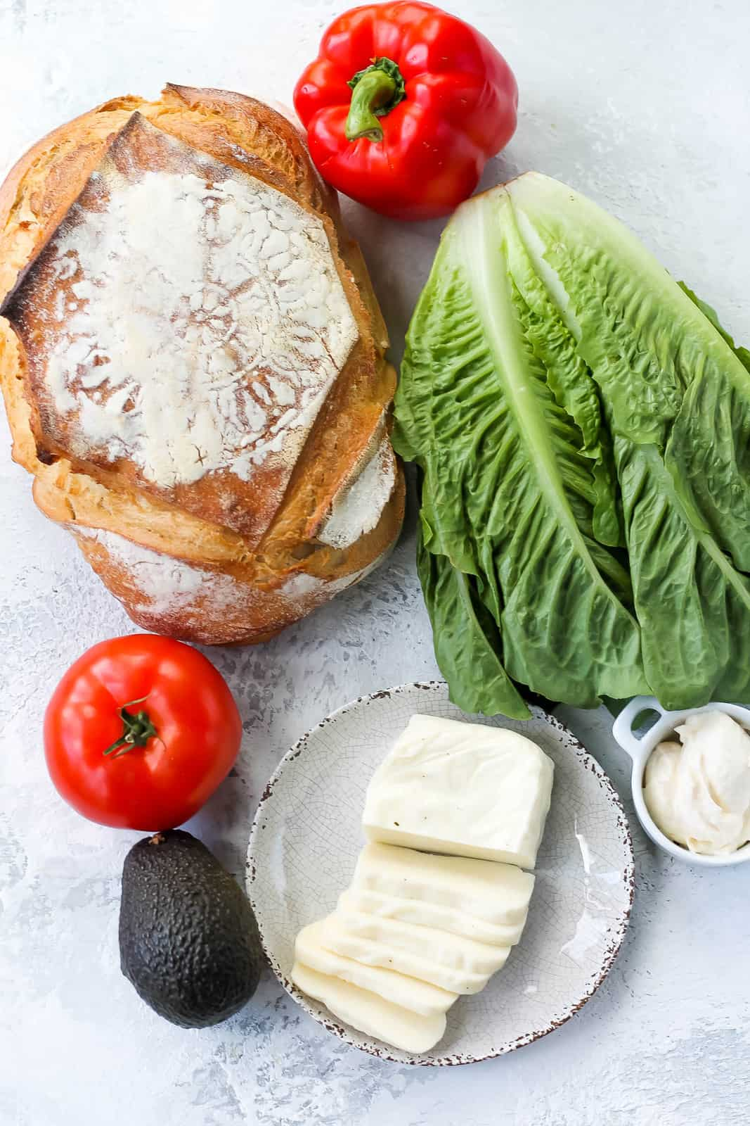 a loaf of bread, red pepper, lettuce, tomato, avocado, and halloumi cheese on a grey background
