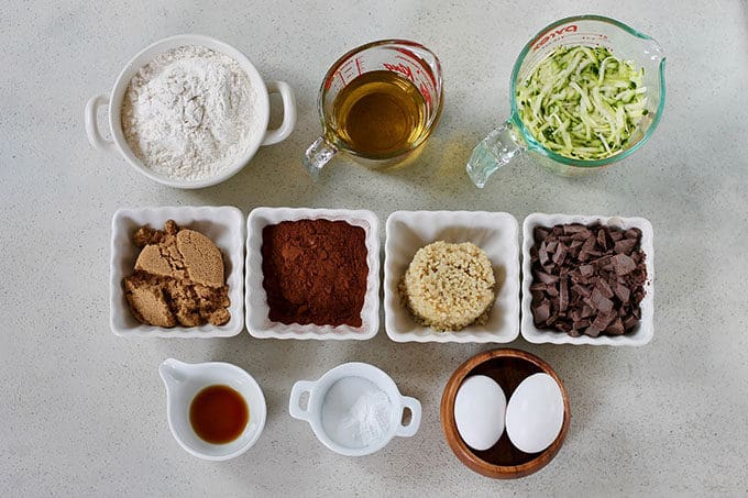 flour, oil, zucchini, sugar, cocoa, quinoa, chocolate, vanilla, and eggs on a grey background