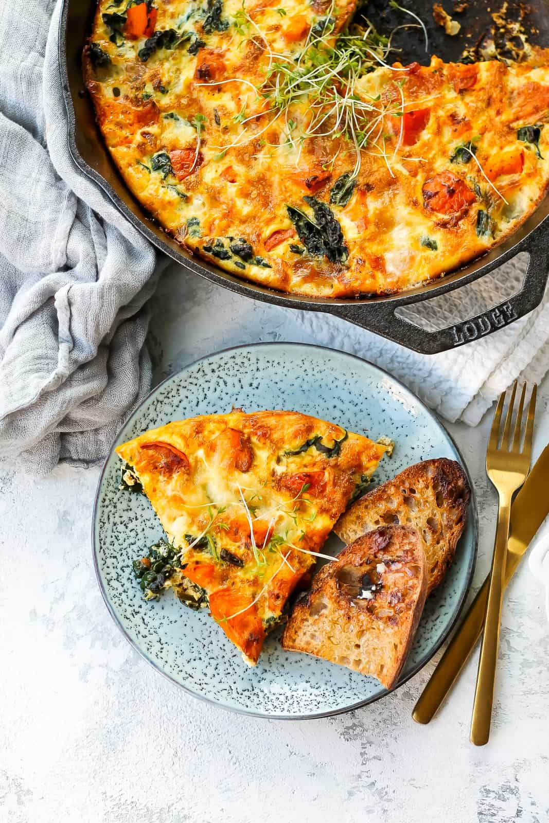 pumpkin frittata in a cast iron frying pan with a blue plate of frittata to the side