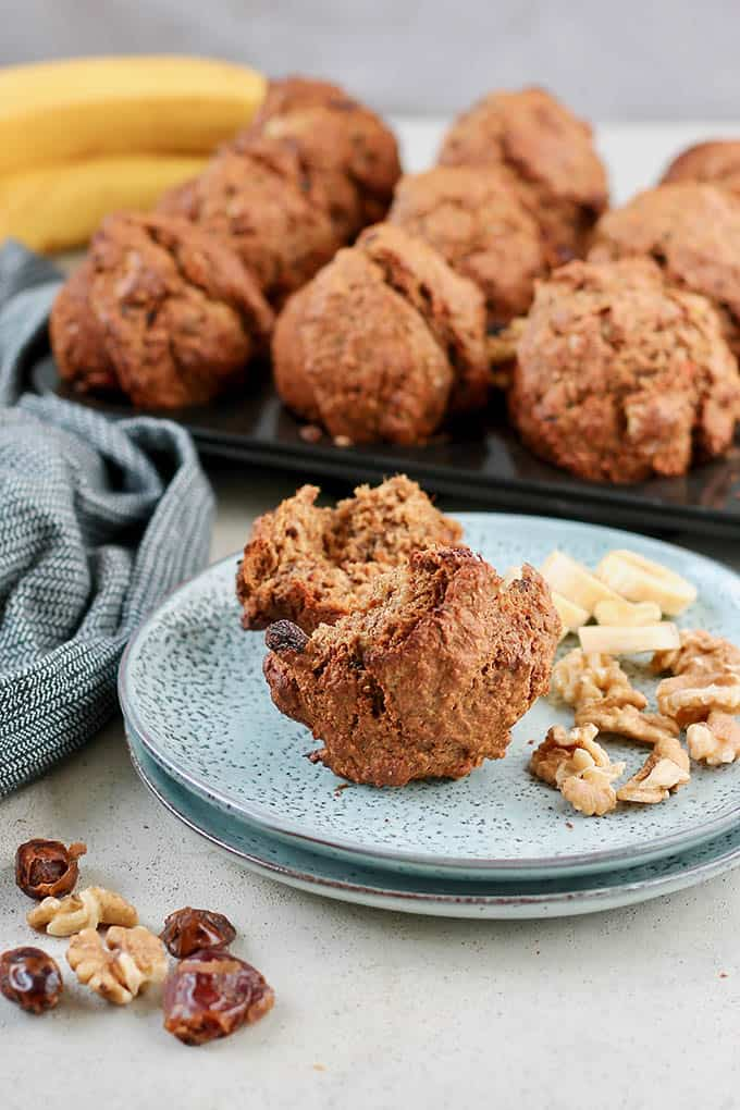 a banana bran muffin on a blue plate with walnuts and banana chunks