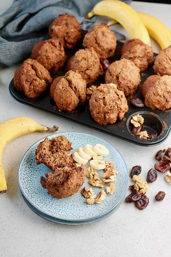 three bananas and banana bran muffins on a grey background