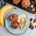 banana bran muffins on a blue plate with a banana to the side
