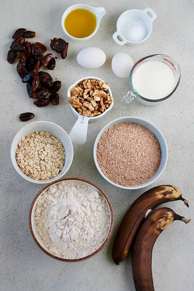 bananas, eggs, dates, walnuts, bran, oats, flour, milk, and oil on a grey background