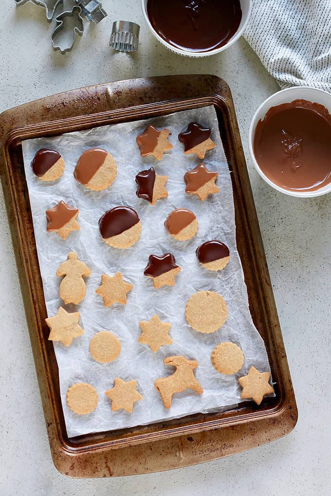 a tray of brown sugar shortbread cookies being dipped in milk and dark chocolate
