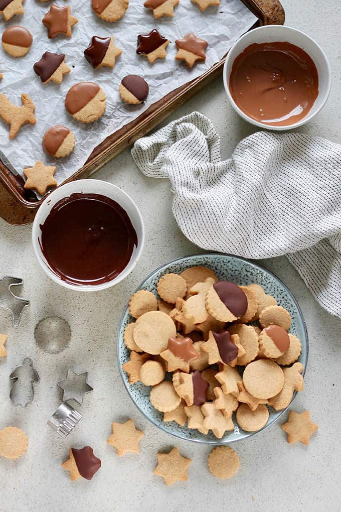chocolate dipped shortbread cookies on a tray beside a bowl of chocolate and a white tea towel