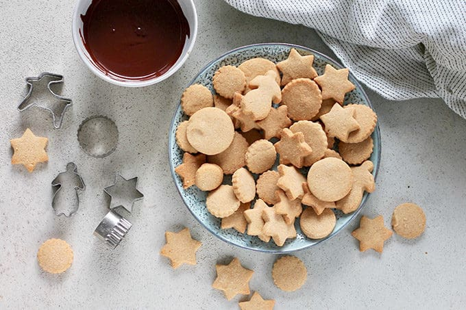 overhead photo with a plate of brown sugar shortbread cookies, a bowl of melted chocolate, and some cookie cutters on a grey background