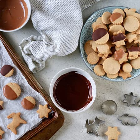 a plate of brown sugar shortbread cookies, some cookie cutters, and a tray of chocolate dipped cookies