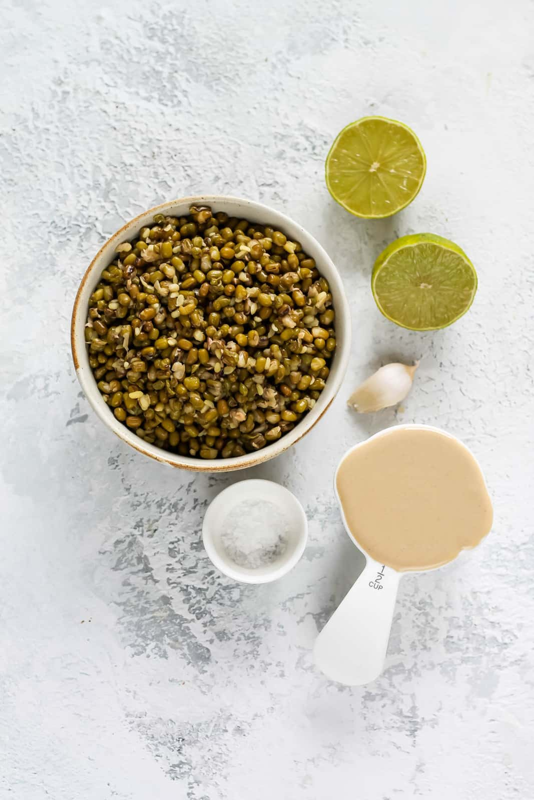 cooked mung beans, tahini, limes, salt, and garlic on a grey background