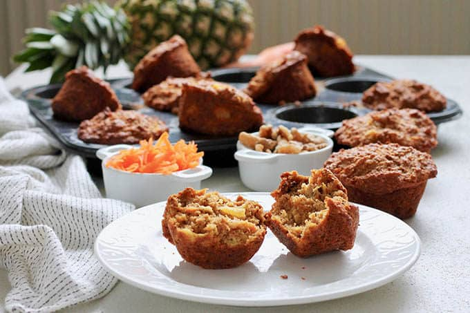 a carrot pineapple muffin on a white plate with muffins, shredded carrot, and a pineapple in the background