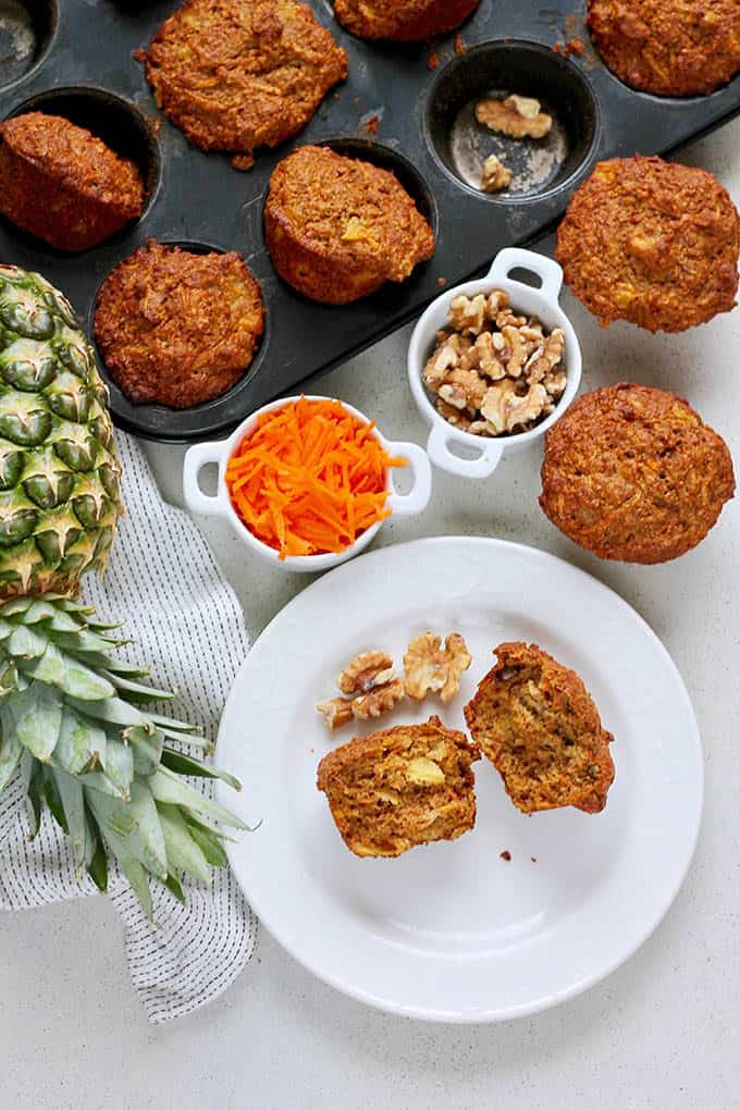 carrot pineapple muffins on a grey surface with a pineapple and a bowl of shredded carrots to the side