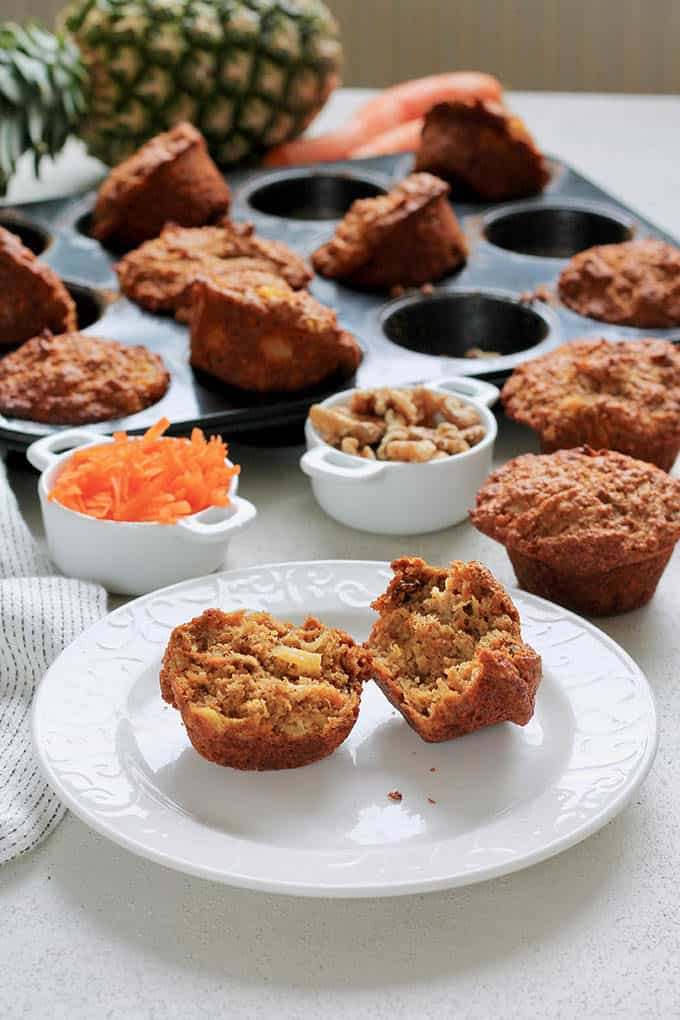 a carrot pineapple muffin split in half on a white plate with more muffins in the background