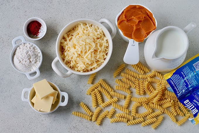 cheese, flour, spices, pasta, pumpkin, and milk on a grey background