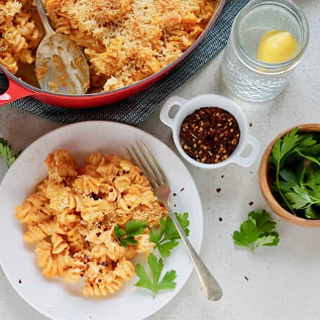 a plate of pumpkin mac and cheese with a casserole dish and spices in the background
