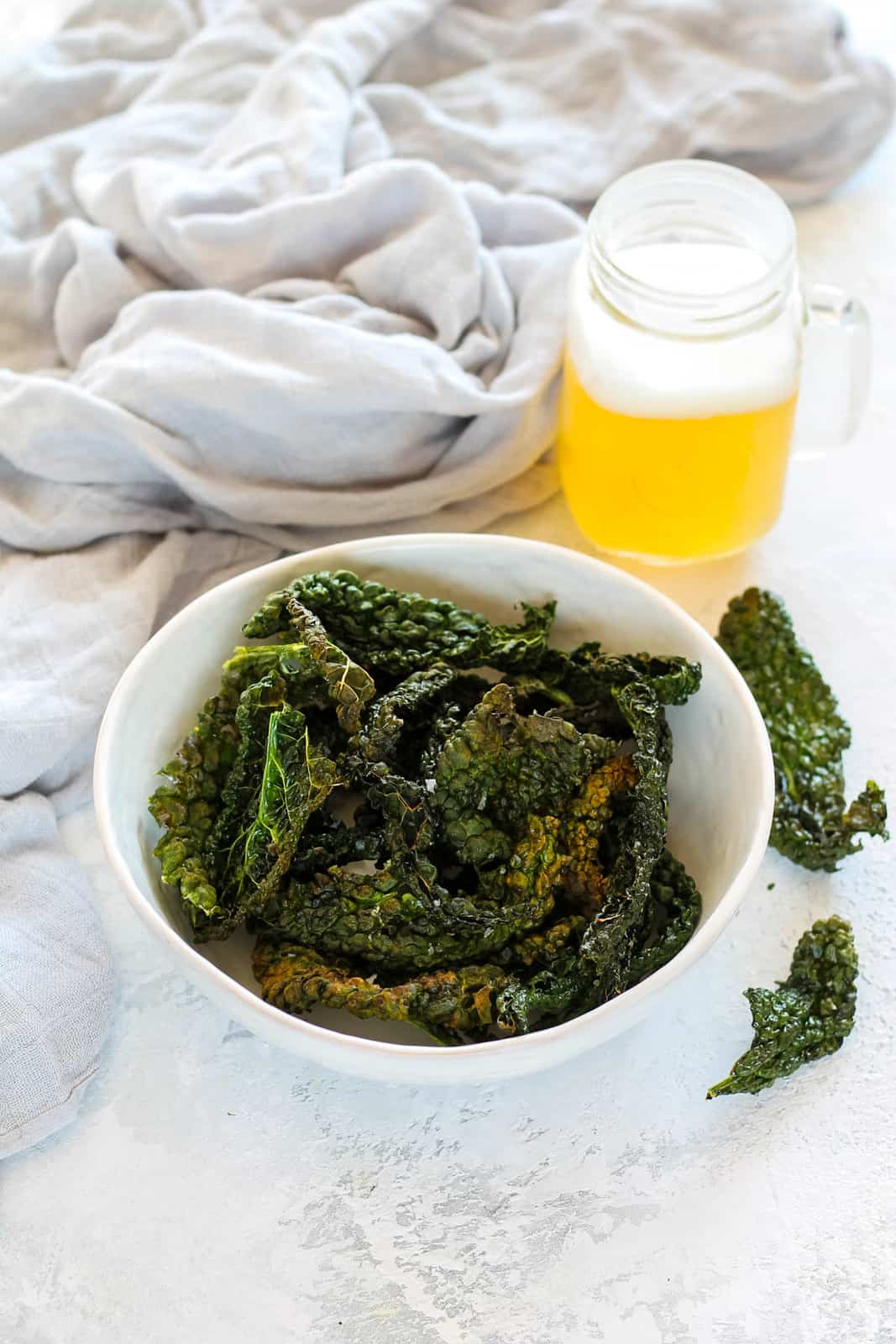 air fryer kale chips in a white bowl with a mug of beer in the background
