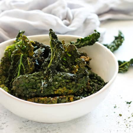 a bowl of kale chips on a grey background
