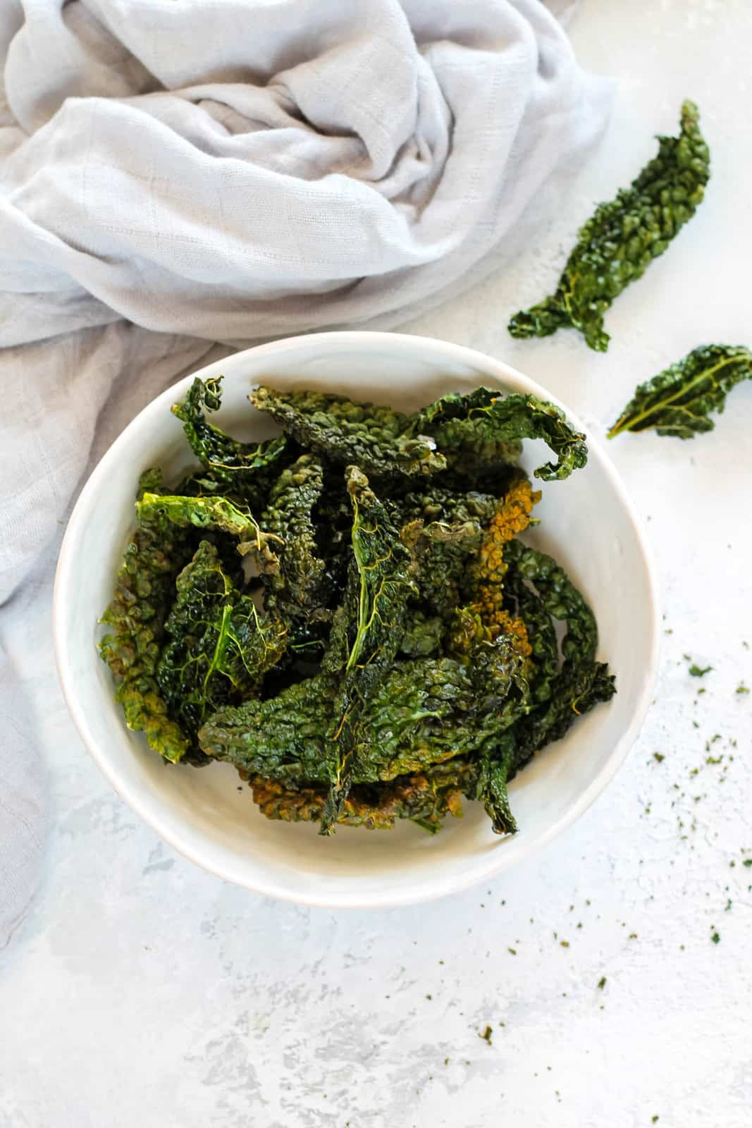 overhead photo of air fryer kale chips in a white bowl