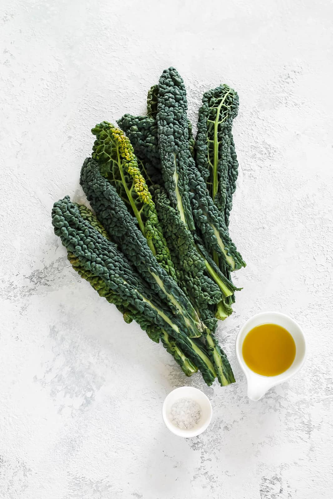 kale, olive oil, and salt on a grey background
