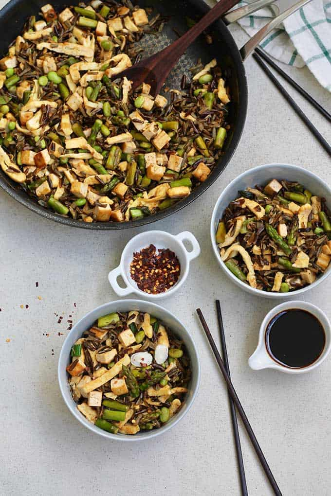 overhead shot of fried wild rice with asparagus and egg in two bowls with chopsticks, chili flakes, and soy sauce in the background
