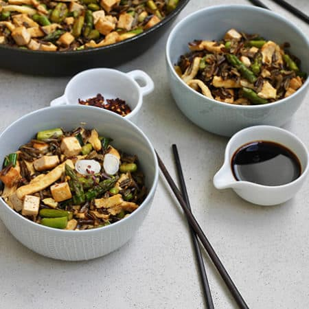 fried wild rice with asparagus and egg in blue bowls with chopsticks and soy sauce in the background