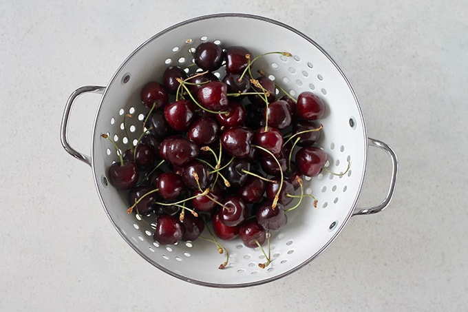 a white colander full of cherries