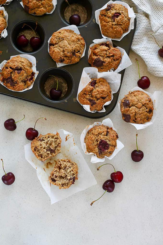 overhead photo of a tin of cherry muffins with one muffin removed and broken in half, and some cherries scattered around