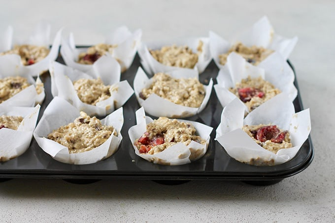 muffin batter spooned into parchment lined muffin cups