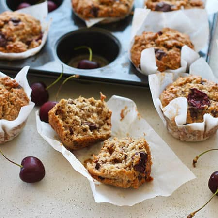 a tray of cherry muffins on a grey background with a couple of muffins removed from the tin and fresh cherries scattered around