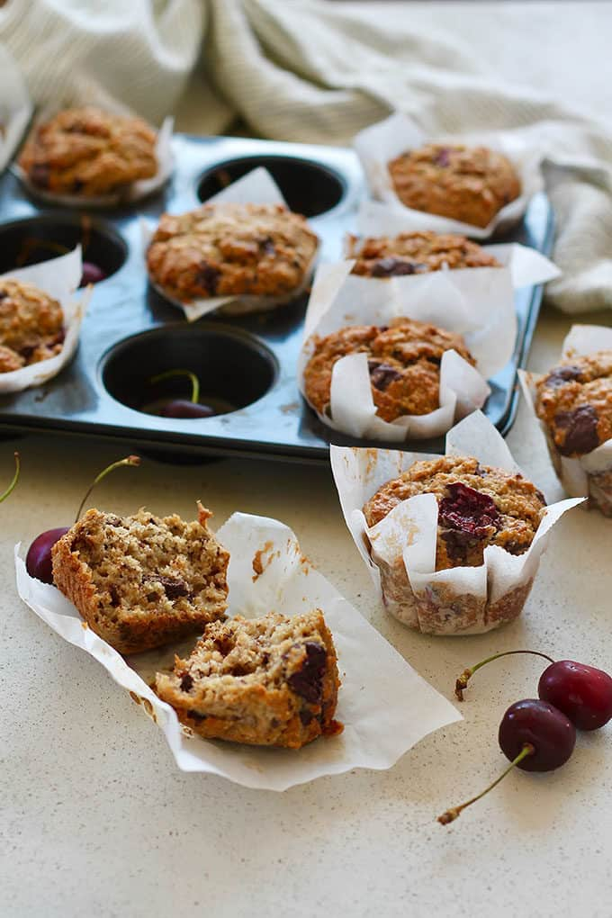 a tray of cherry muffins on a grey background with fresh cherries scattered around