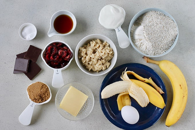 chocolate, brown sugar, cherries, butter, oatmeal, yoghurt, banana, egg, and flour on a grey background