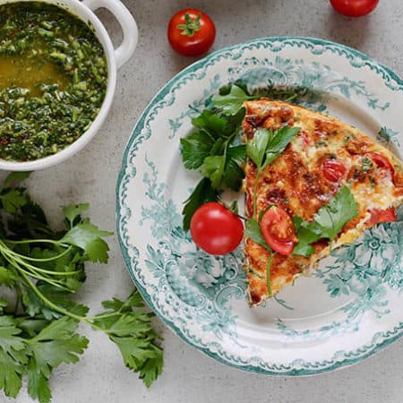 vegetarian frittata with corn and tomatoes on a blue and white plate on a grey background