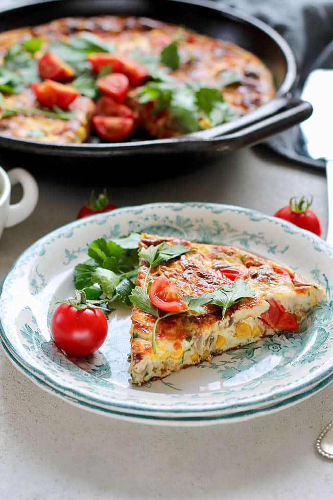 vegetarian frittata with corn and tomatoes on a blue and white plate with cherry tomatoes and parsley