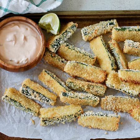 A parchment linked baking sheet of baked zucchini fries