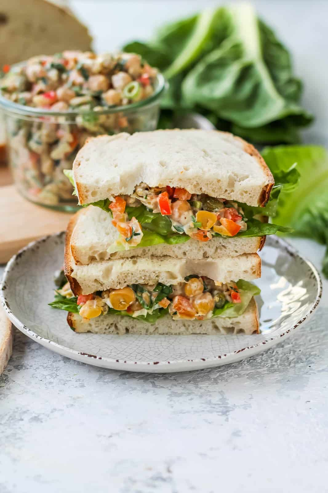 close up photo of a stacked chickpea salad sandwich on a white plate