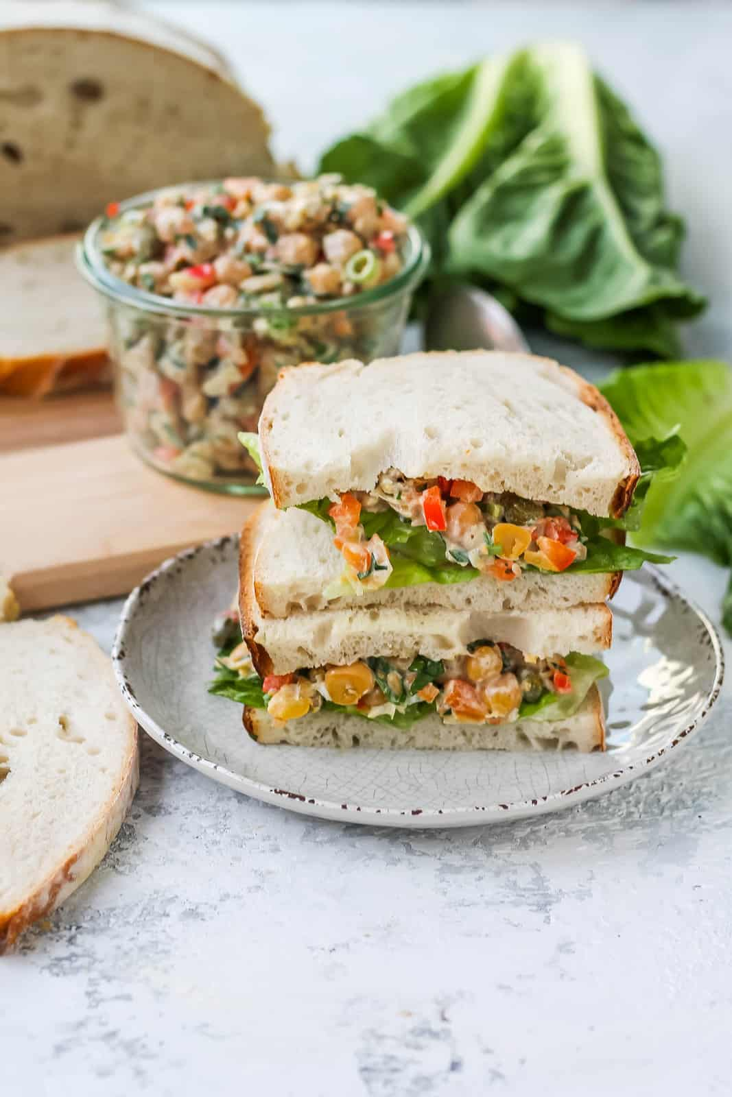a chickpea salad sandwich stacked on a white plate with a jar of chickpea salad in the background
