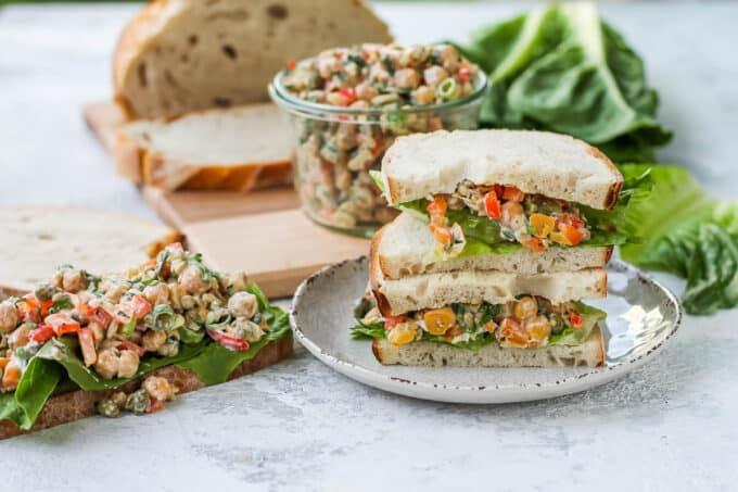 a chickpea salad sandwich on a white plate with a loaf of bread in the background
