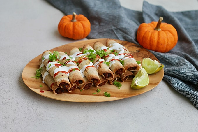 pumpkin and black bean taquitos on a wooden platter