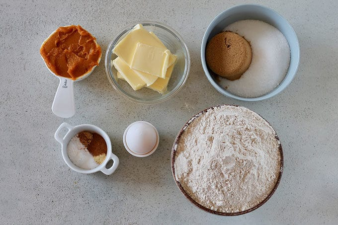 pumpkin, butter, sugar, spices, egg, and flour on a grey background