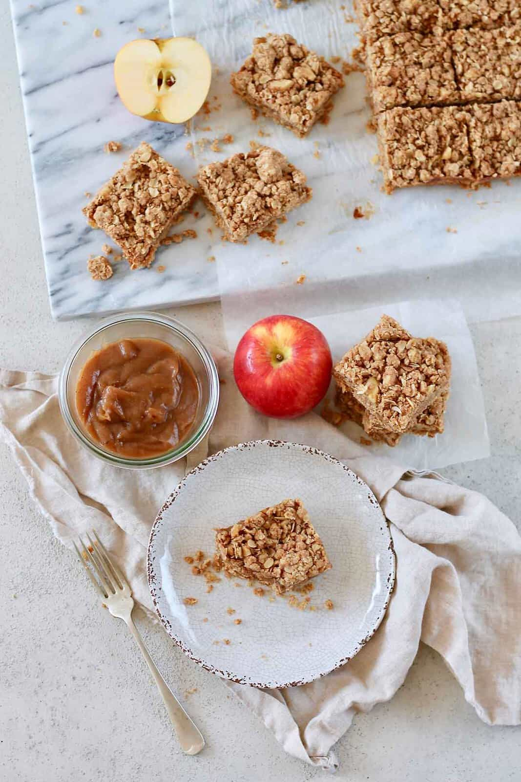 apple crumble bars on a marble surfafce with apples and apple butter