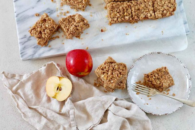 apple crumble bars on a grey background and one bar on a plate with a fork