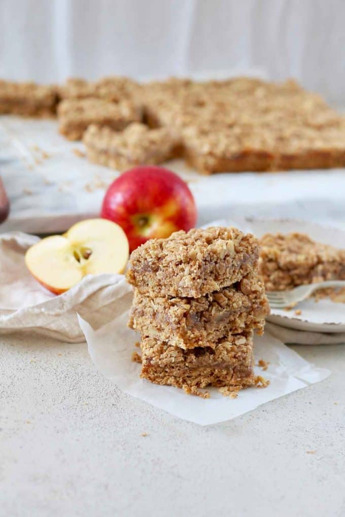 close up photo of three apple crumble bars in a stack