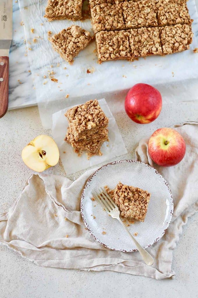 overhead photo of apple crumble bars with three apples on a marble background
