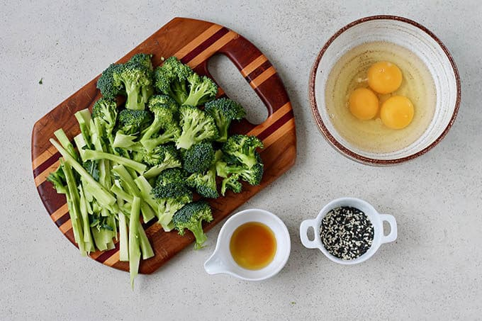 broccoli, eggs, sesame seeds, and sesame oil on a grey background